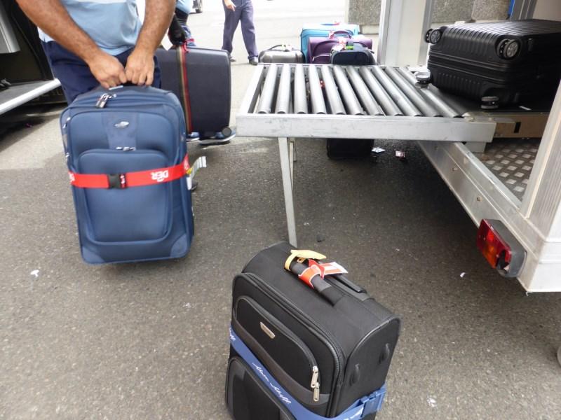Der Koffer wird am Bus ausgeladen