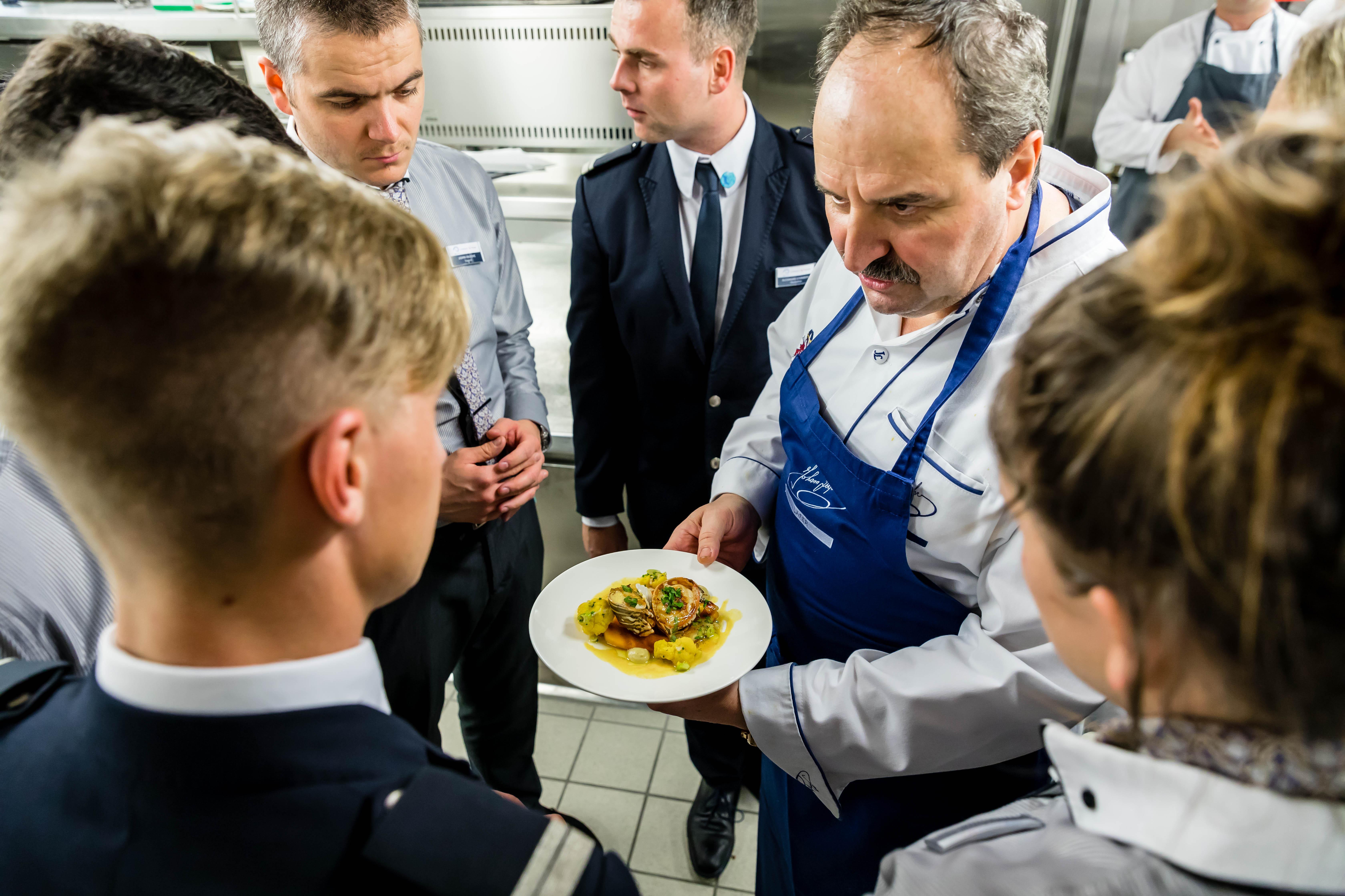 Mein Schiff Gastkoch Johann Lafer erklärt den Kellnern die Gerichte