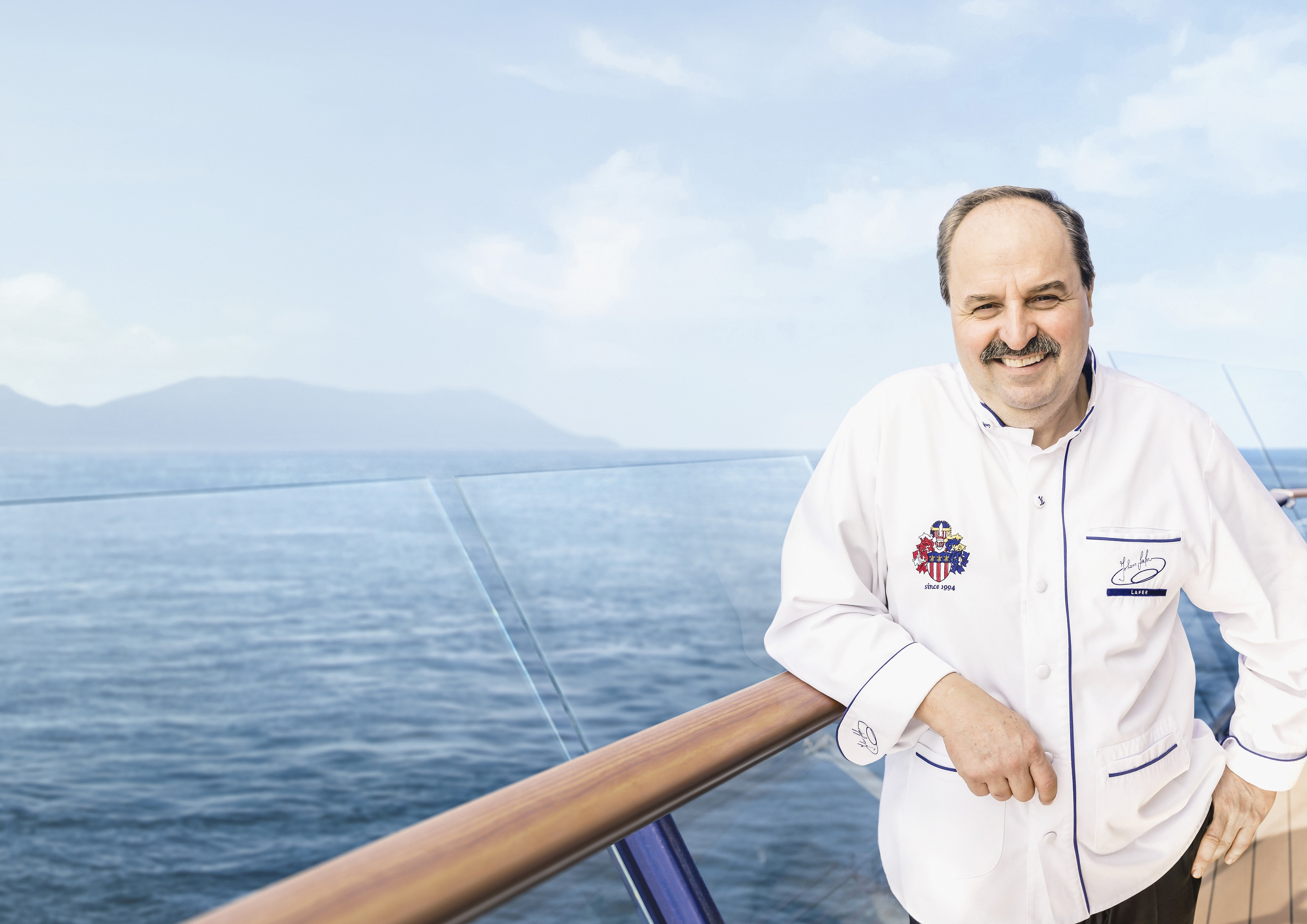 Johann Lafer an der Reling auf der Mein Schiff Flotte von TUI Cruises