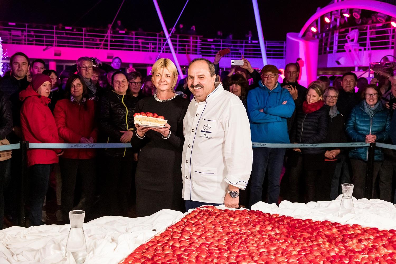 Johann Lafer und Anja Fichtel und die riesengroße Torte bei der Premierenfeier der Mein Schiff Herz